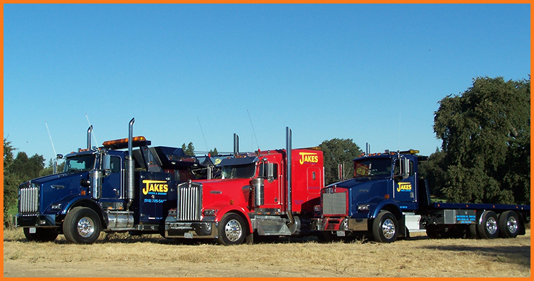 Three tow trucks parked beside each other||||