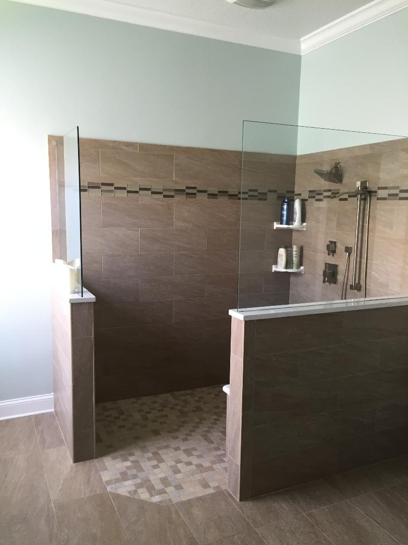 Walk in shower featuring two half glass panels with decorative band of tile.