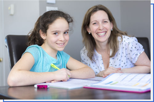 Mature Mother Helping her Child With Homework at Home