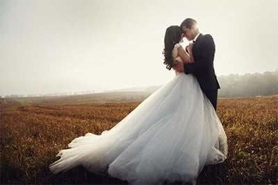Newlywed Couple In Field At Sunset
