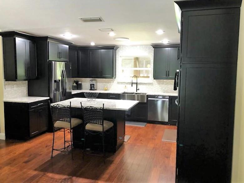 Glamorous Kitchen with black cabinetry, quartz countertops, and an eye popping backsplash.