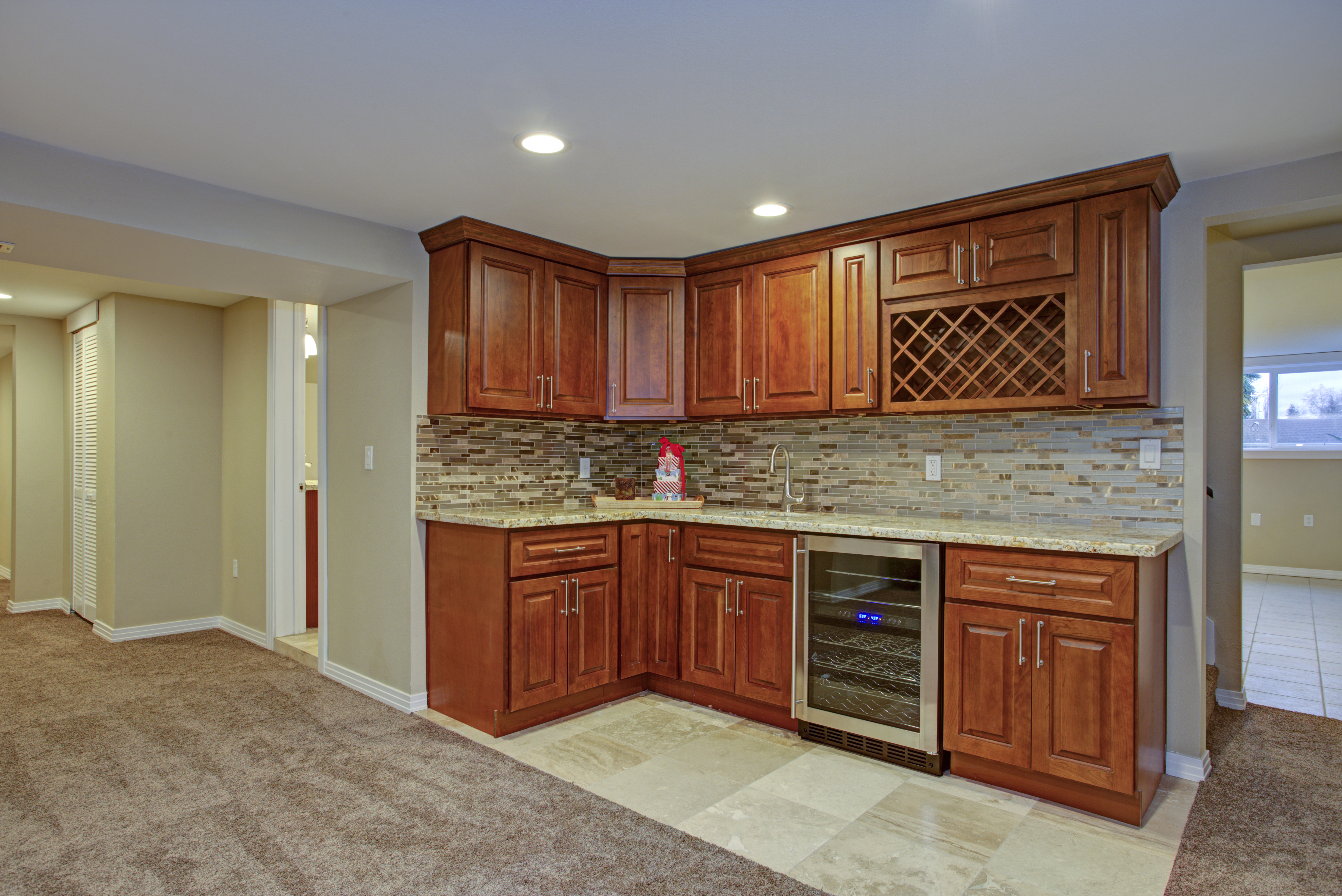 Basement remodel with kitchenette including quartz countertop with drop mount sink, cooler and mosaic backsplash.