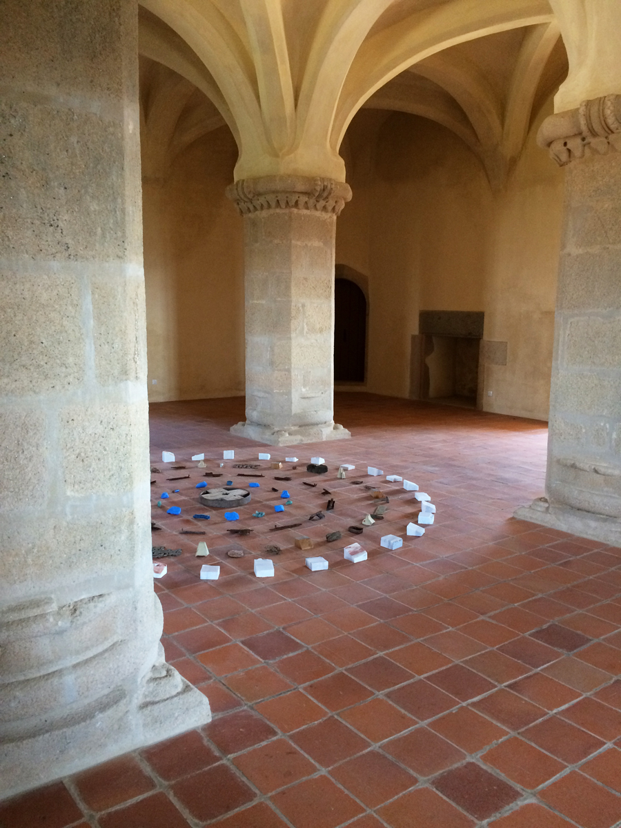 Rustic objects arranged in concentric circles on a tile floor in a castle-like space.
