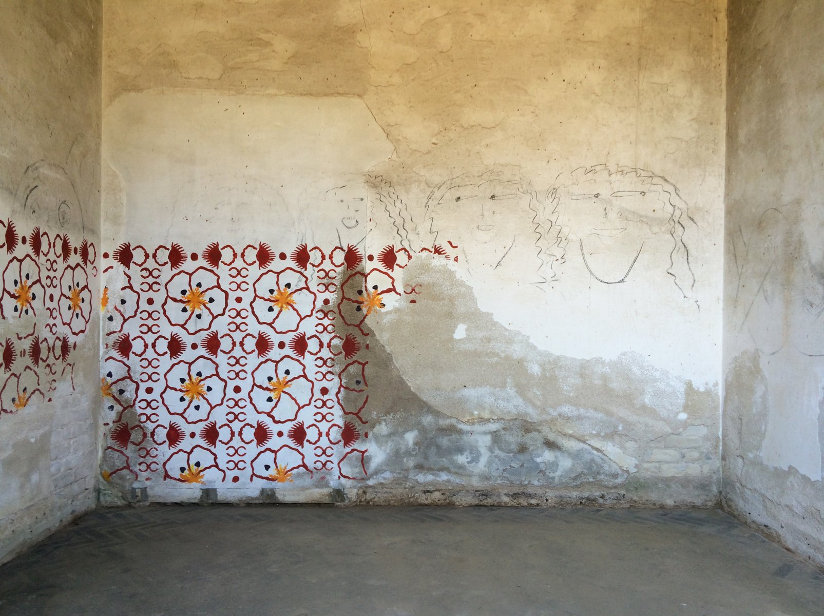 An empty rustic whitewashed room with a floral mural and charcoal-drawn faces.