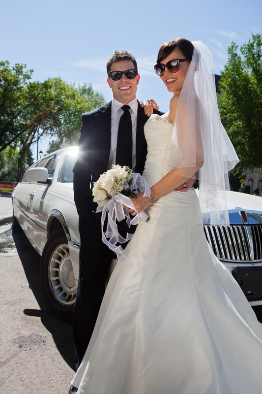 Newly married couple beside limousine||||
