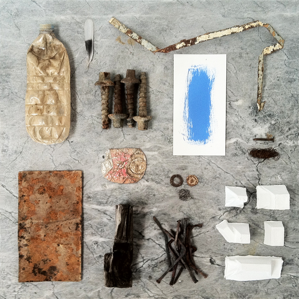A feather, a blue painting on paper and other objects on a grey marble table.