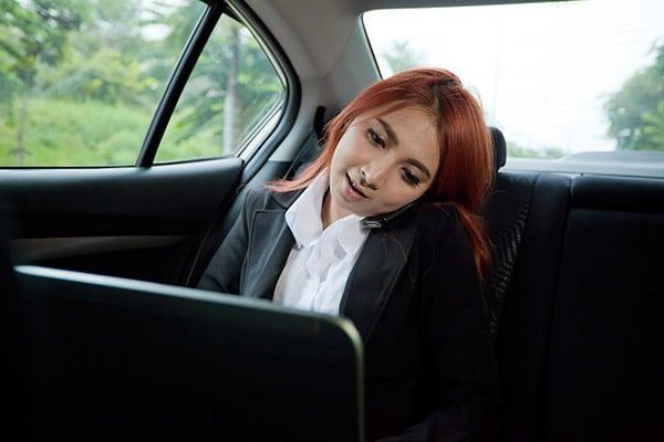 Woman using laptop in car