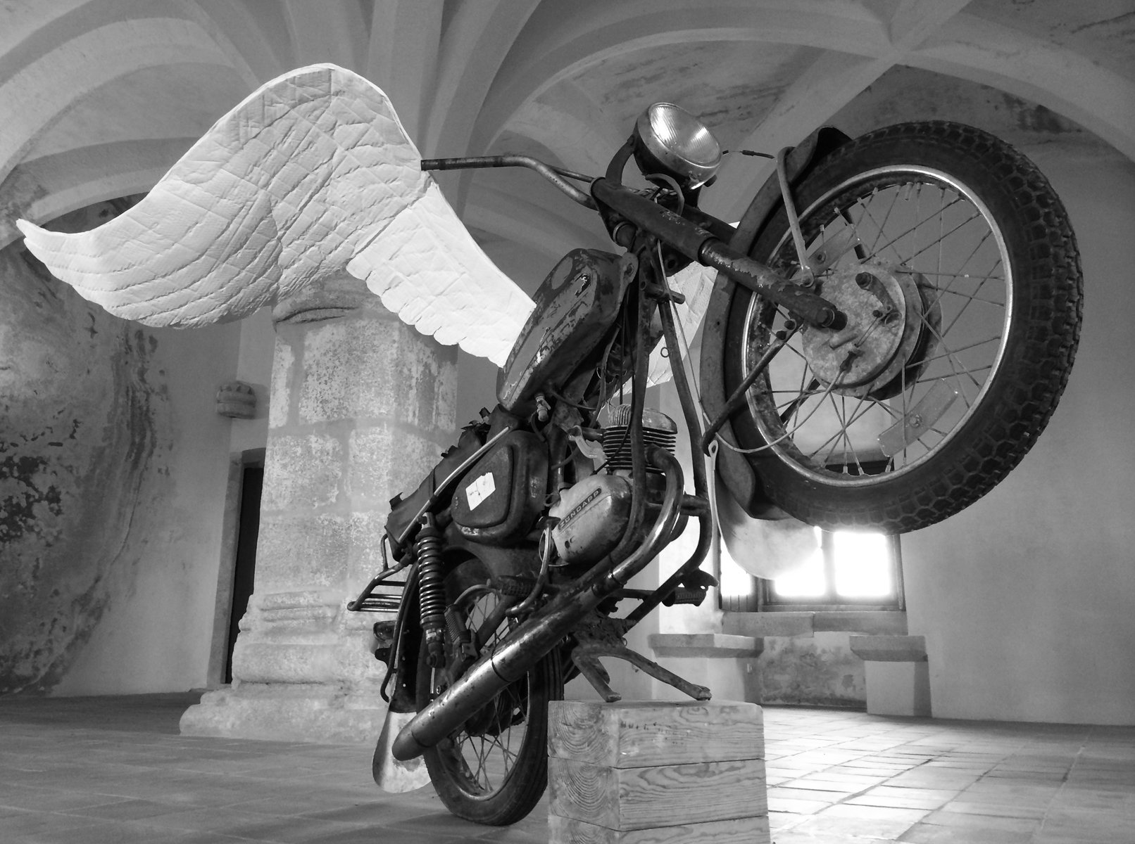 A rearing motorcycle with large white wings in a room with a vaulted ceiling.