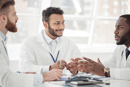 Doctor Discussing With Affiliates During Meeting
