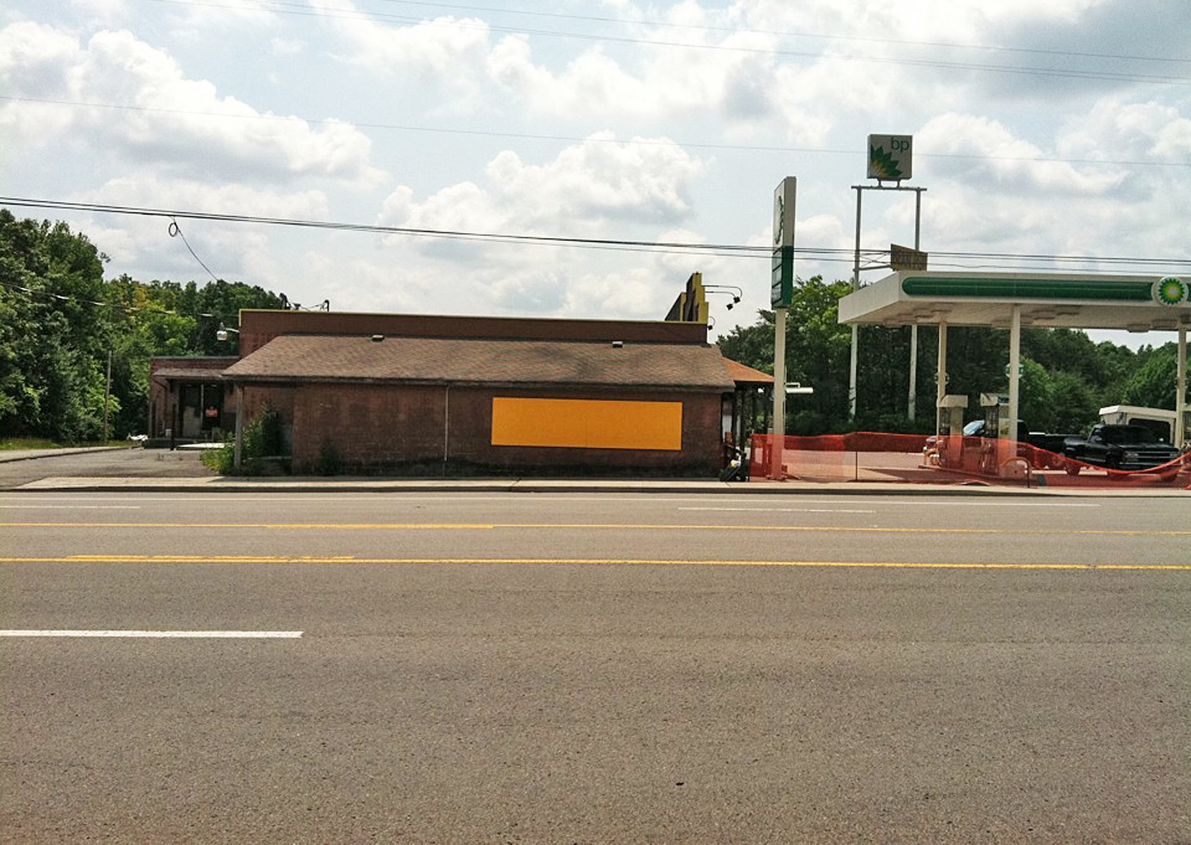 A minimalist yellow rectangle on a low brick building next to a BP gas station.
