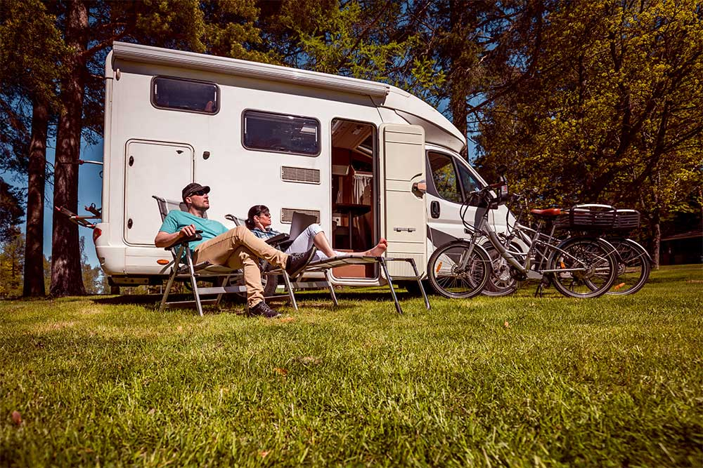 Woman with a Man Resting near Motorhomes in Nature