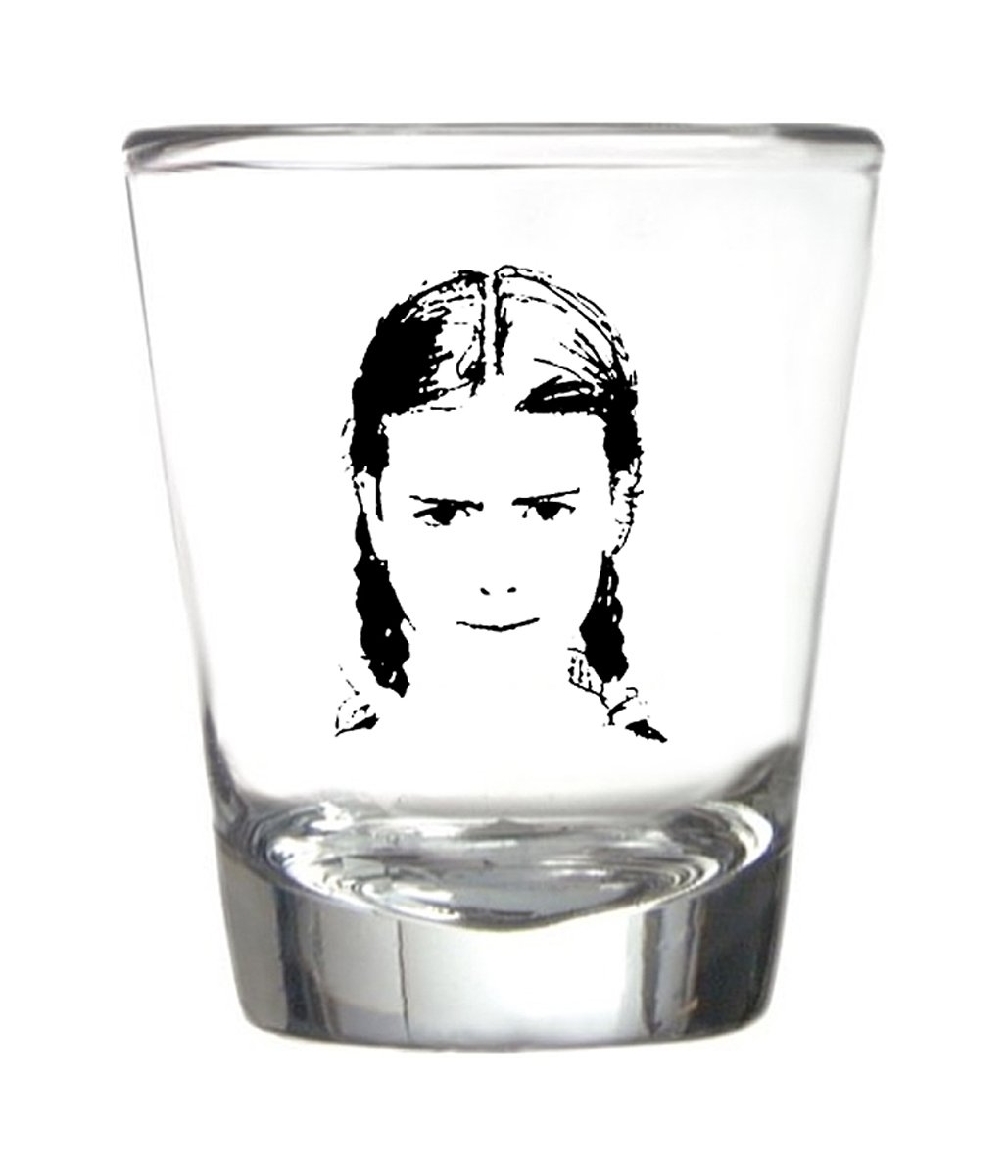 A black line drawing on a shot glass of a serious looking young girl with pigtails.