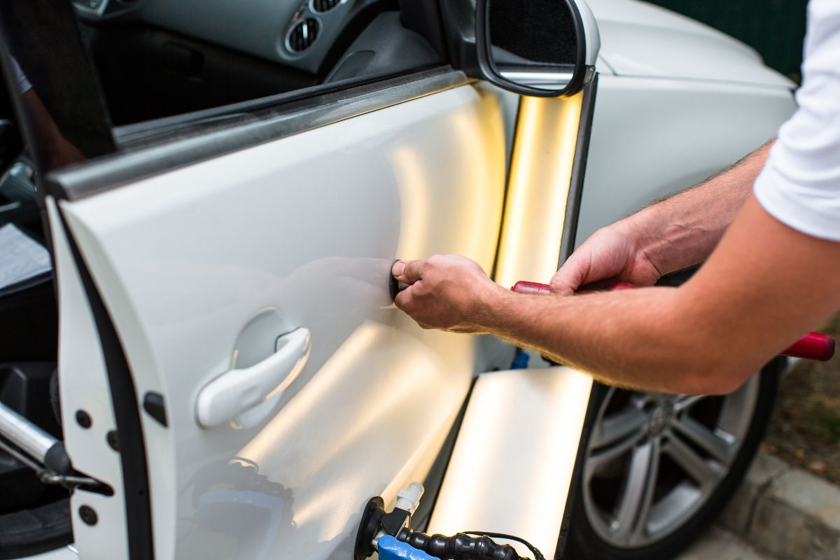 Repairing car dent after the accident by paintless dent repair