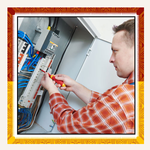 Electrician Works With Screwdriver In Fuse Box