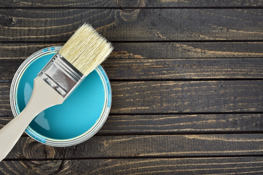 A paint brush resting on a can of sky blue exterior house paint