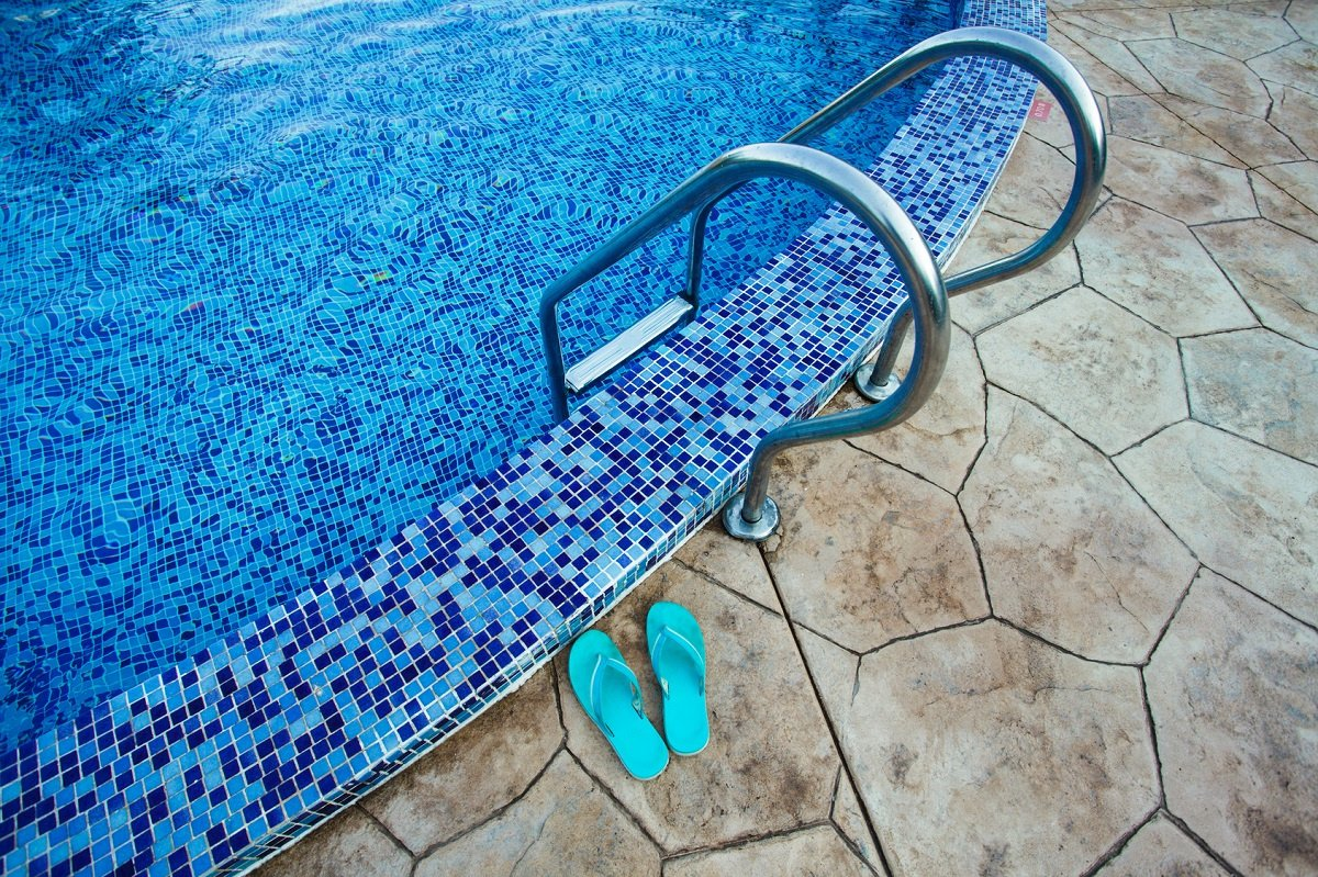 Flip flops sit on the edge of a residential swimming pool.