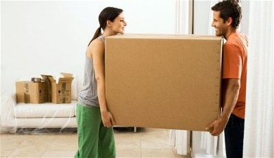 man and woman carrying large box
