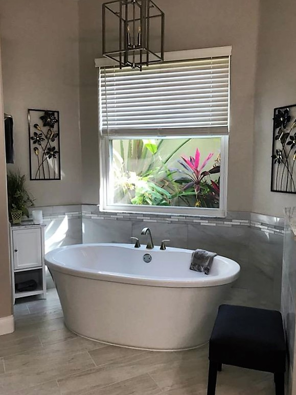 Spa like oasis with free standing soaking tub featuring large grey tile and mosaic surround.