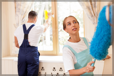 Young Maid and Her Colleague Cleaning a Room