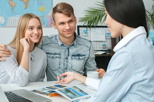 Young Couple in a Tour Agency Communication with a Travel Agent
