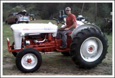 Man on red and white tractor||||