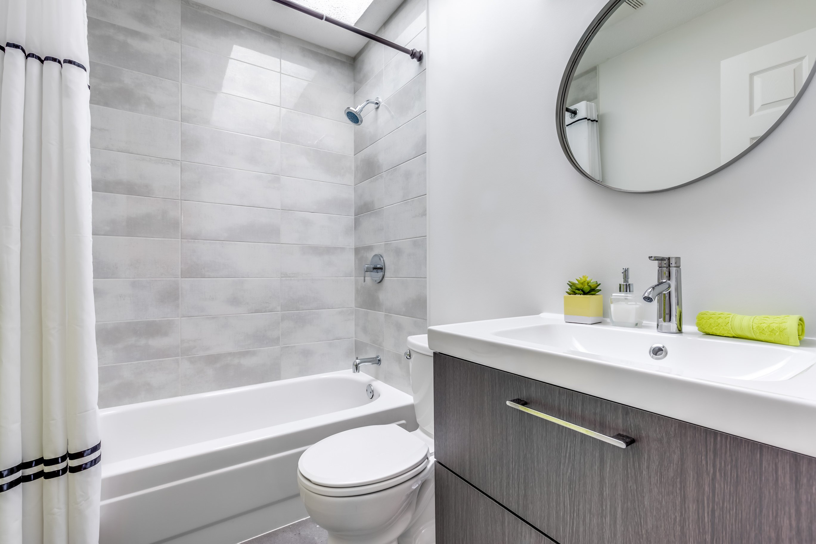 Small Bathroom remodel features beautiful marble tile in the shower with a new toilet and modern vanity with contemporary hardware.