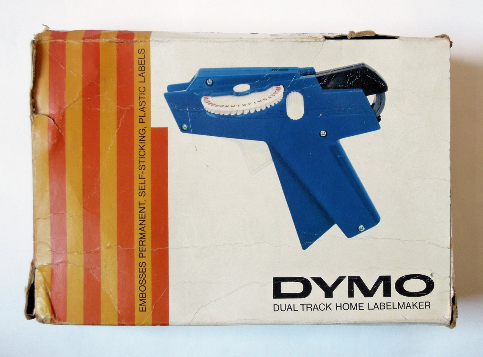"""A vintage Dymo """"dual track home labelmaker"""" box in white, orange and blue."""
