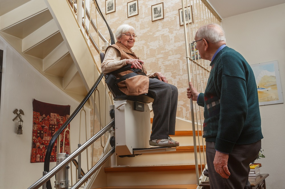 Smiling Older Woman Riding StairLift Upstairs