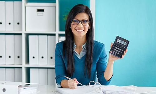 Woman Calculates Tax at Desk in Office