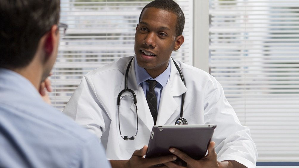 African American Doctor With Tablet And Patient