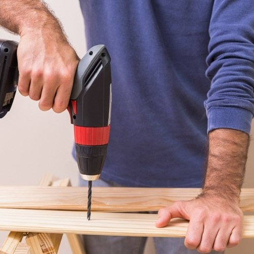 Man Drilling Hole in Plank