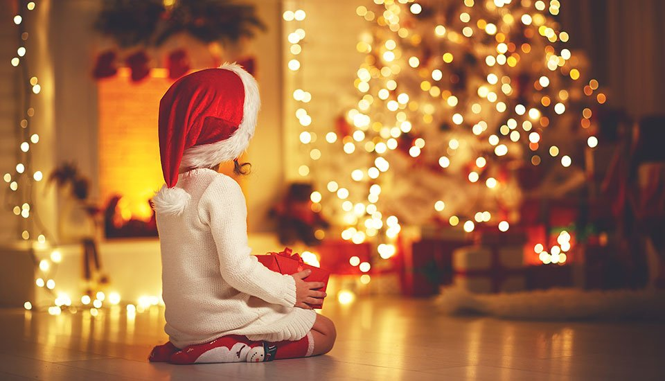 Child Girl Sitting Back in Front of Christmas Tree on Christmas Eve