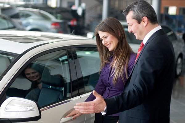 Young woman with car salesperson