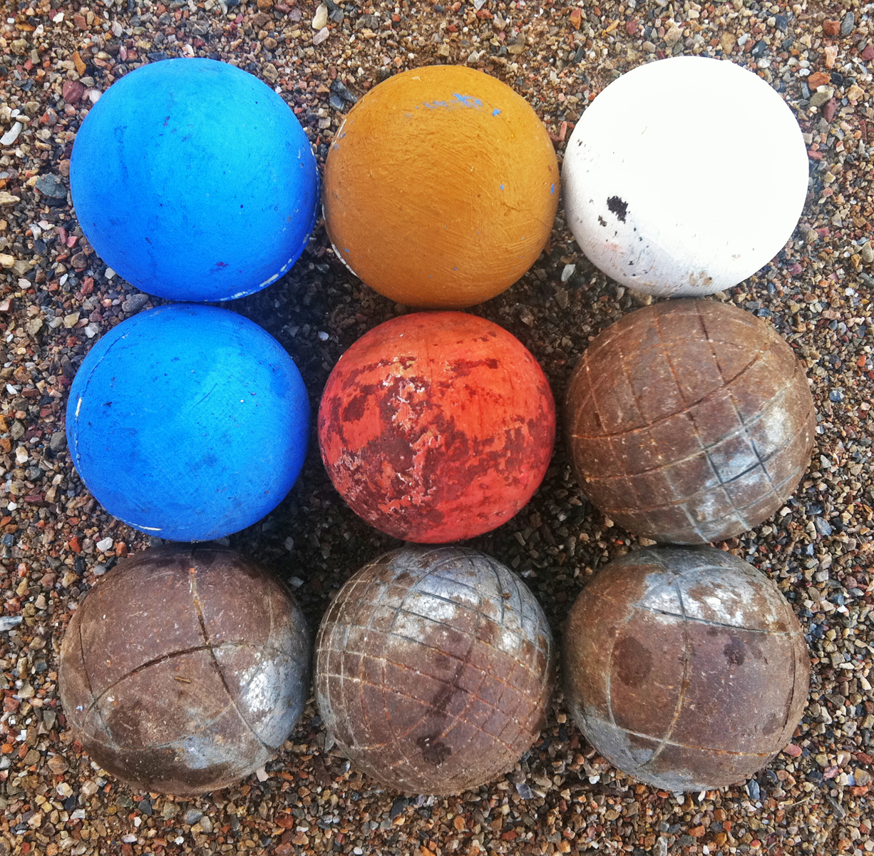 Nine bocci balls, some metal, others bright painted wood, arranged in a square.