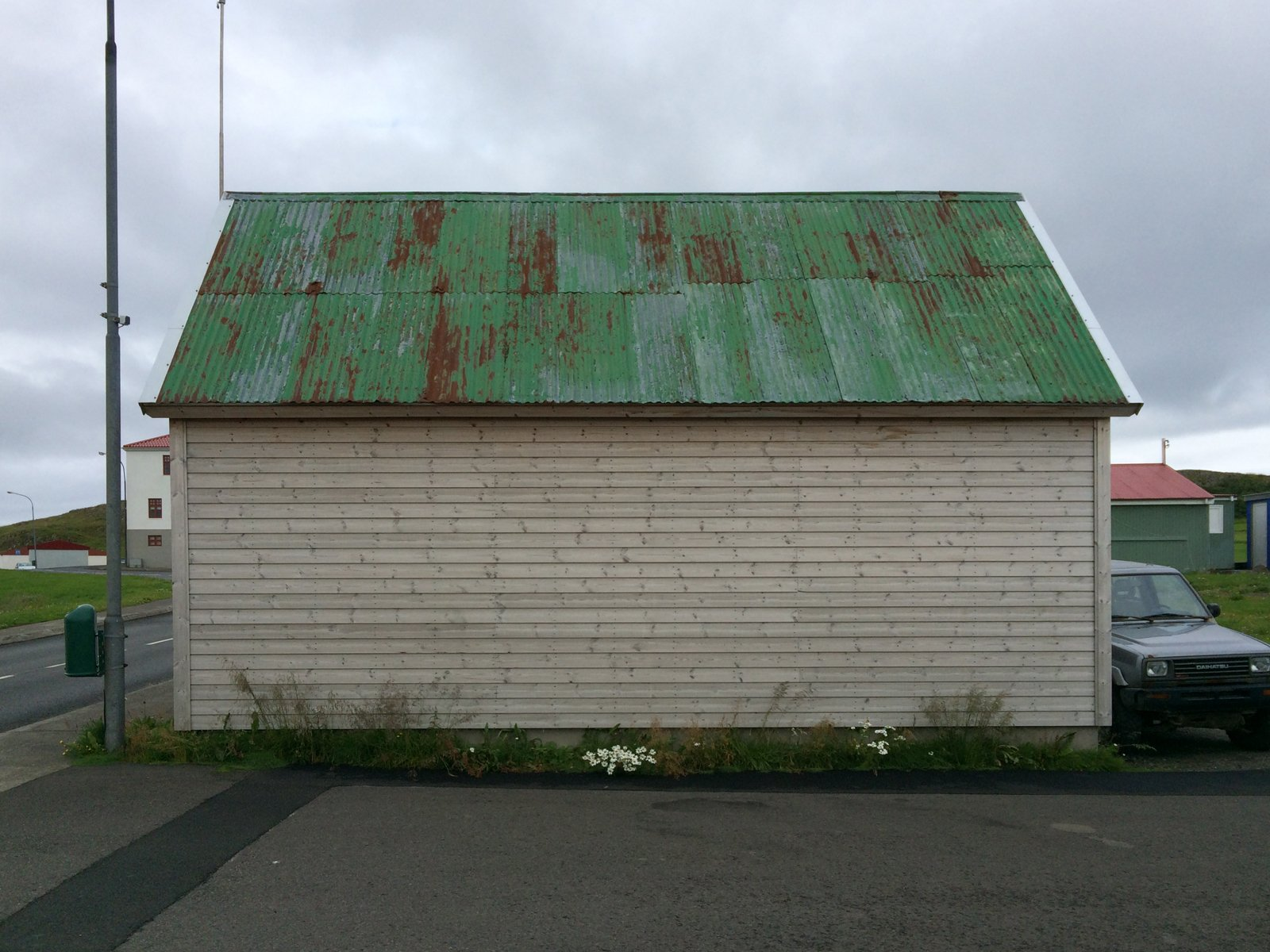 A windowless wall of a white clapboard building with a rusted green metal roof.