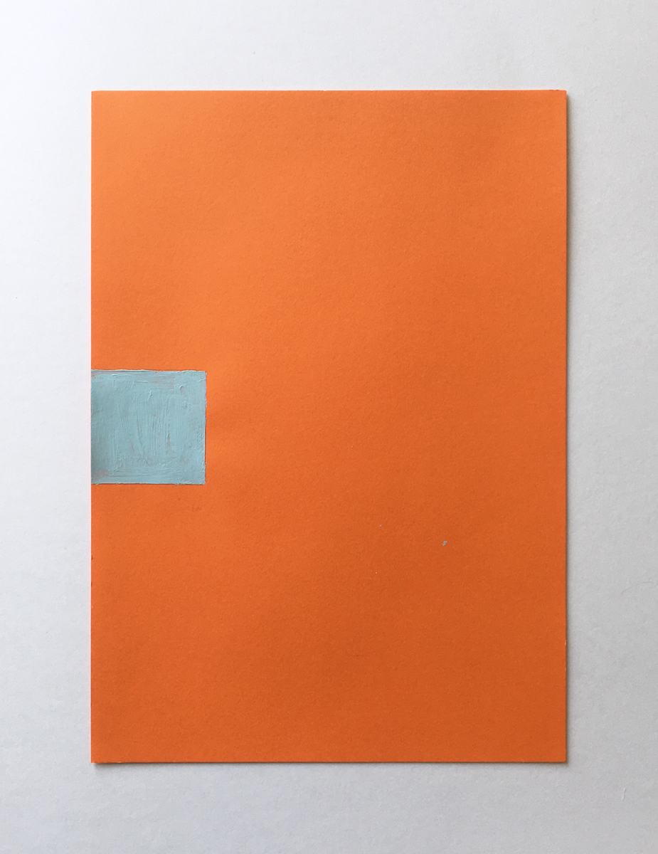 An orange piece of paper with a small square of light blue paint halfway up.