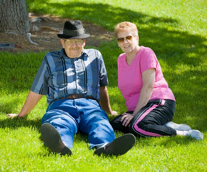 A senior citizen couple reclining on a lawn.