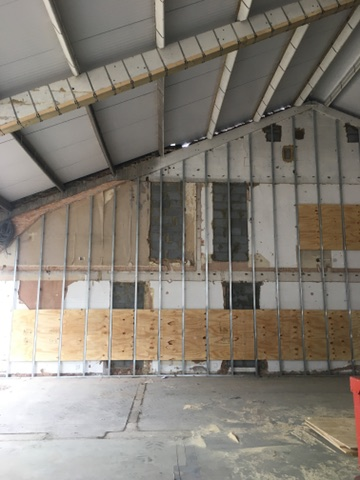 Over cladding old brick wall of first unit