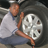 Boy Next to Car Wheel