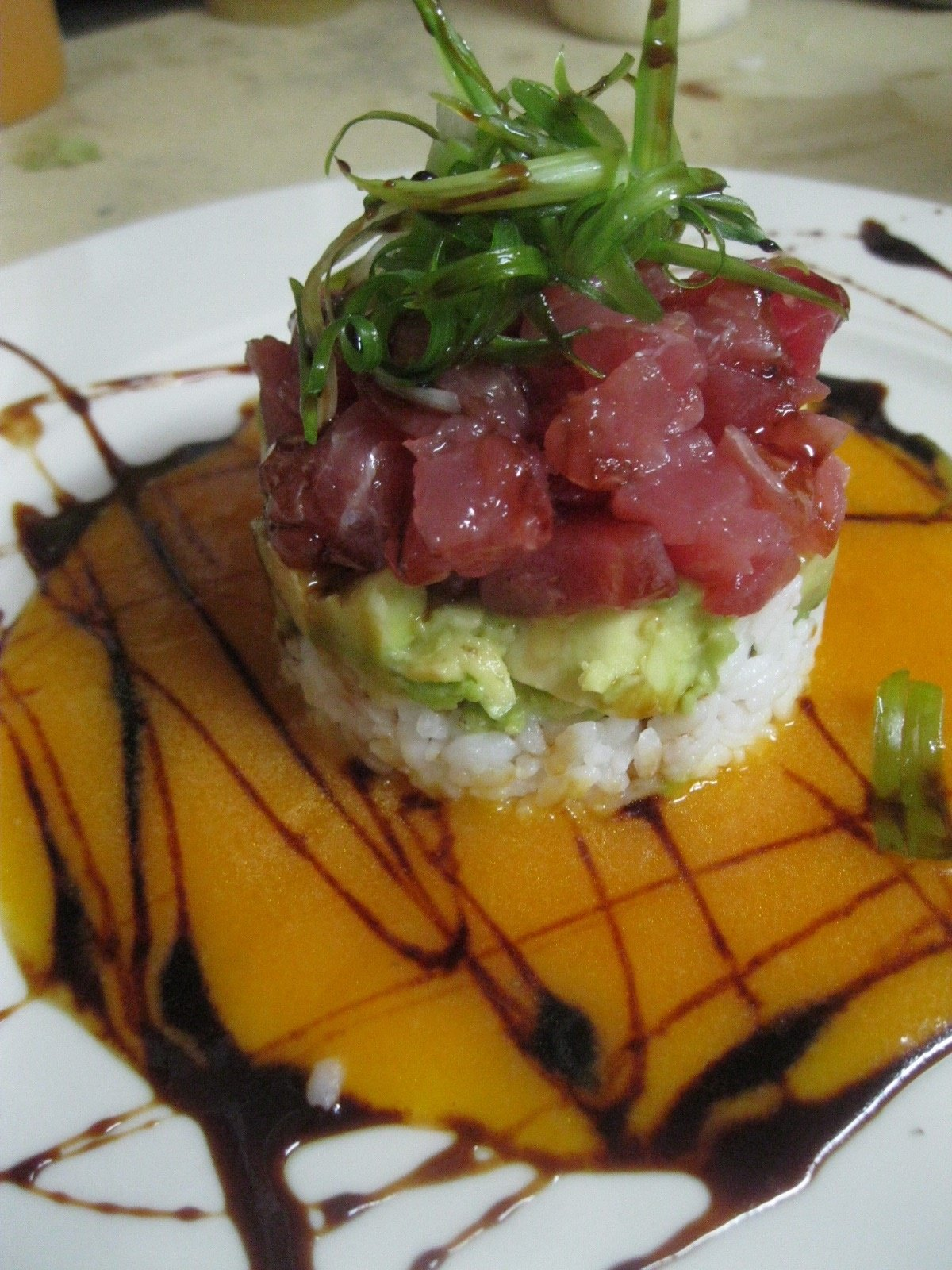 yellowfin tuna poke, avocado and sushi rice tower with a gingered carrot coulis