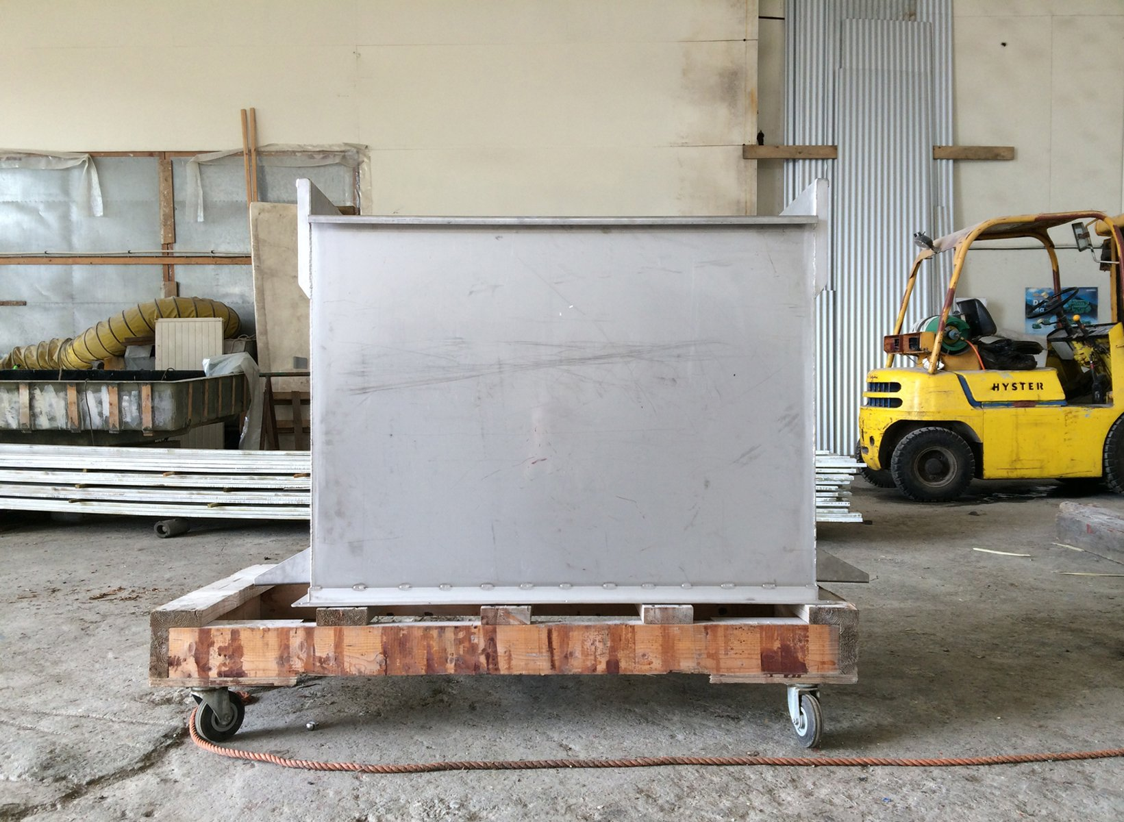 A bare aluminum box sits on a pallet dolly in a warehouse with a yellow forklift.