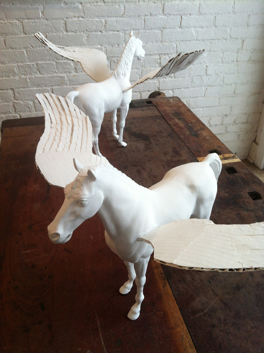 A pair of model horses with cardboard wings, all painted white, on a workbench.