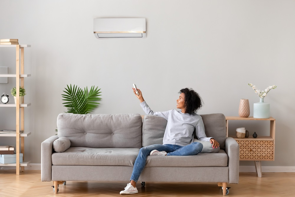 Woman Turning on AC with Remote