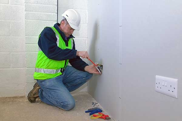 An Electrician Installing An Electrical Socket