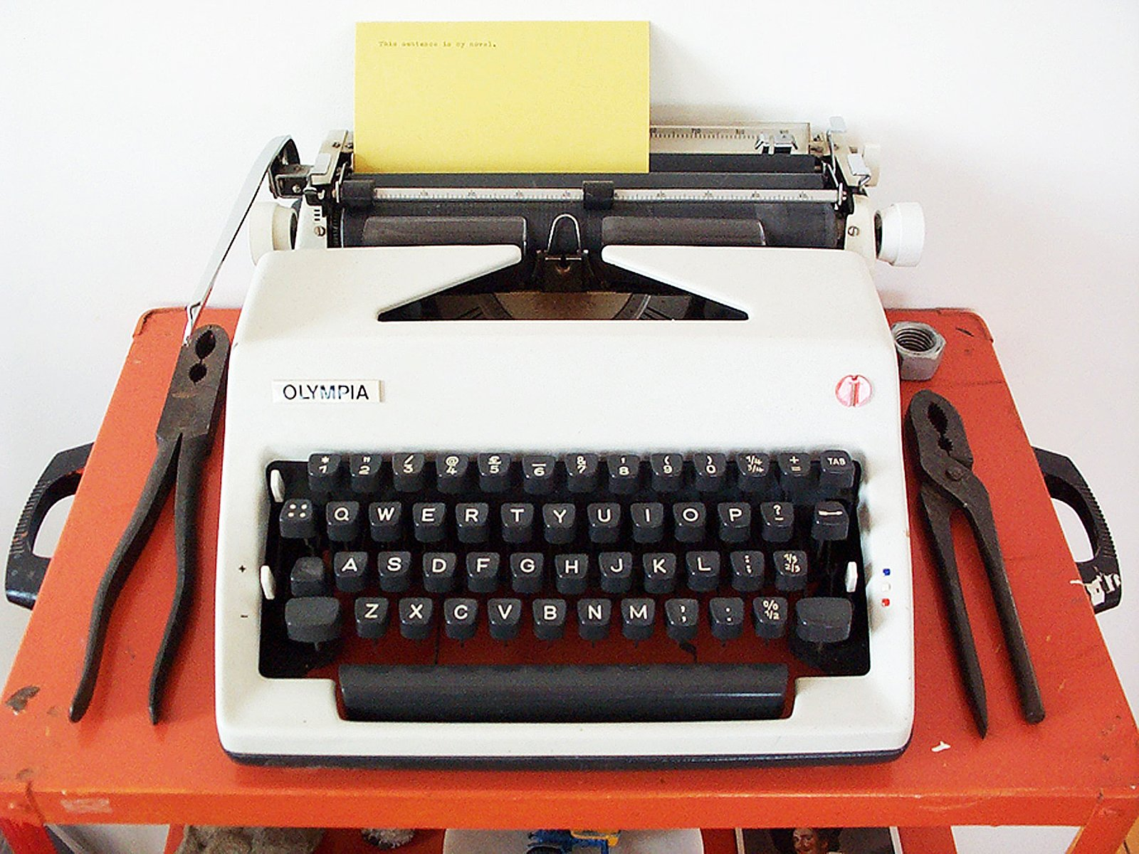 An Olympia typewriter with typed card and two pairs of pliers on an orange cart.