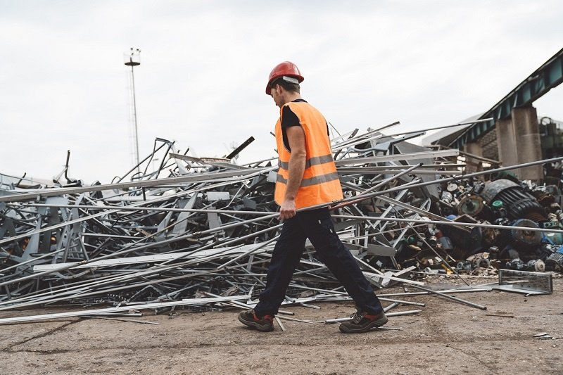 Person Walking in Front of Pile of Scrap Metal