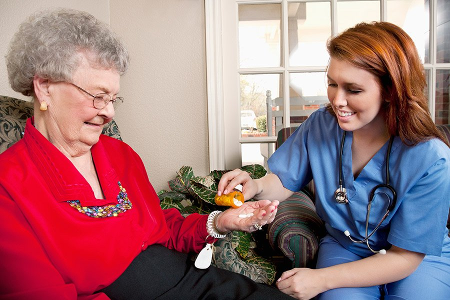 Nurse giving medication to senior adult