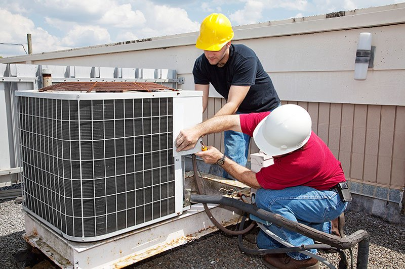Two mans repairing industrial air conditioning