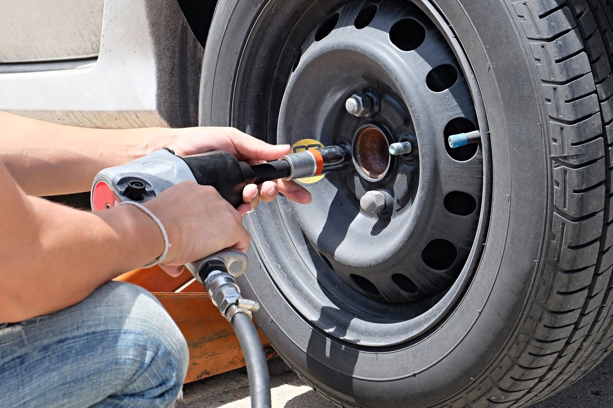 Man Is Changing Tire With Wheel Wrench