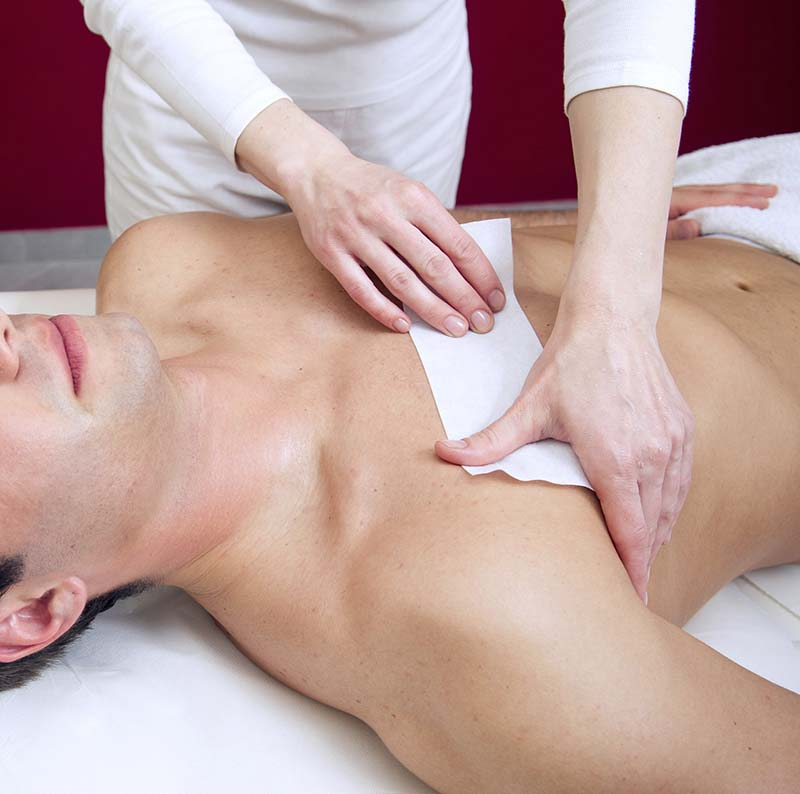 Man receiving waxing in spa